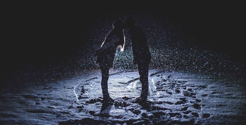 雪の降る外でライトに照らされたカップル