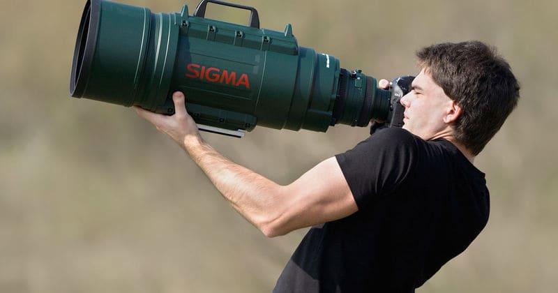 強大な望遠レンズを抱えた男性