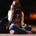 夜中の道路でカメラを構える女性