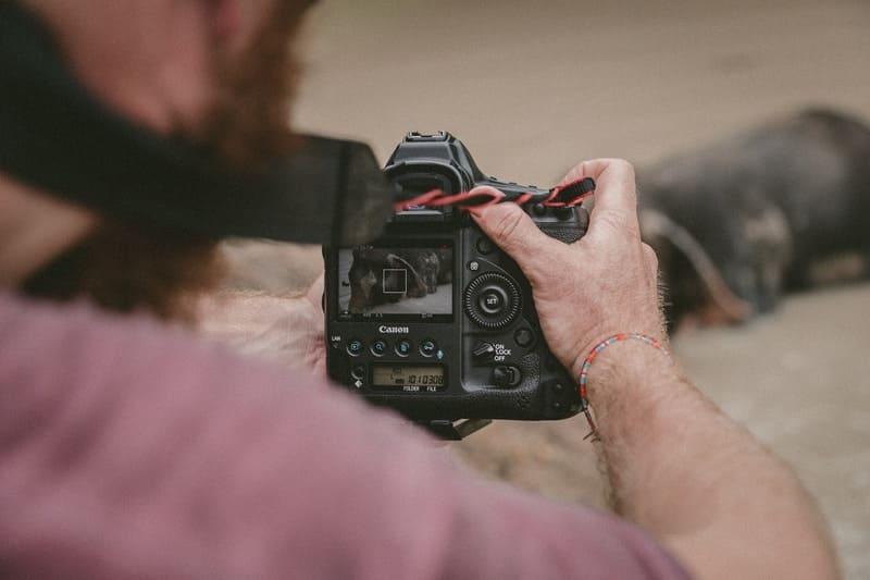 ストラップを首にかけて撮影している男性