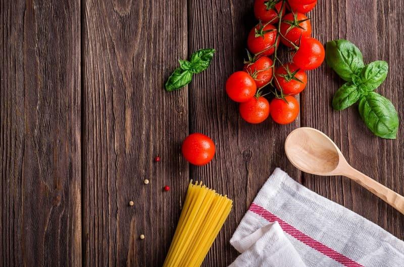 テーブルに置かれたトマトとバジルとパスタ