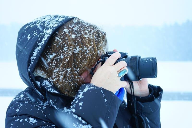 雪の降る中カメラを構える女性