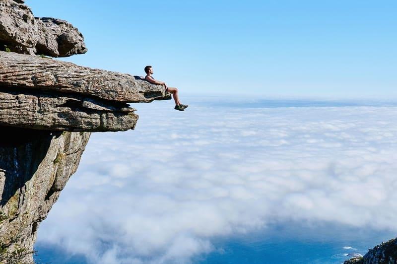 高所の岩場に座っている男性と雲海
