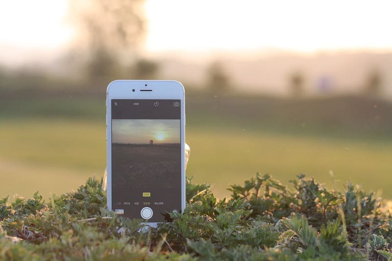 スマホで夕日を撮影している写真