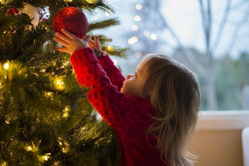 クリスマスツリーに飾りつけする少女