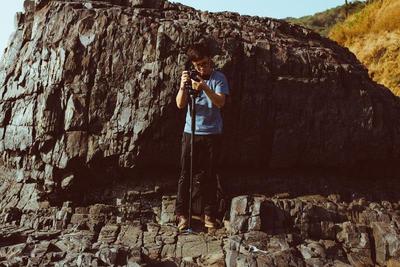 一脚を使ってカメラを構える男性