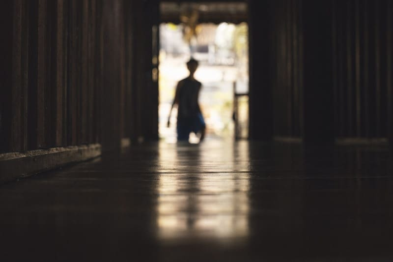 玄関から出ていく人の床とのリフレクション