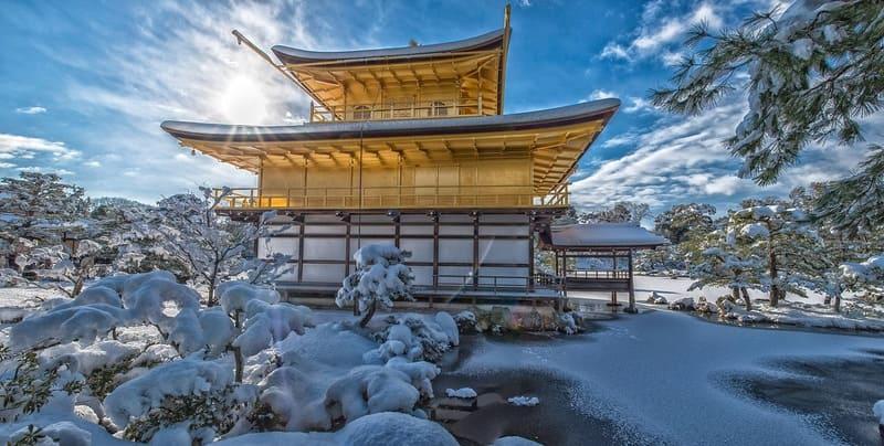 太陽と青空の中の雪の積もった金閣寺