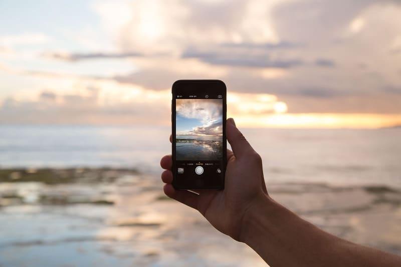 スマホで夕焼けと海を撮影している写真