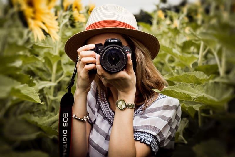 一眼レフを持ったひまわり畑にいる女性