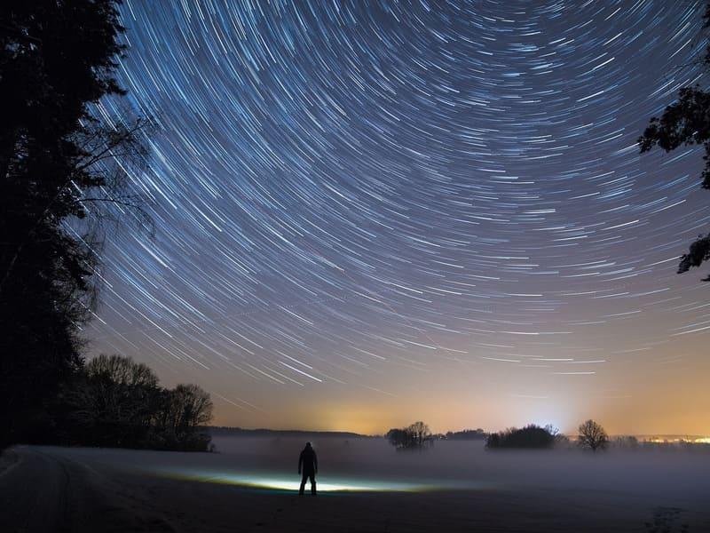 星の光跡と男性