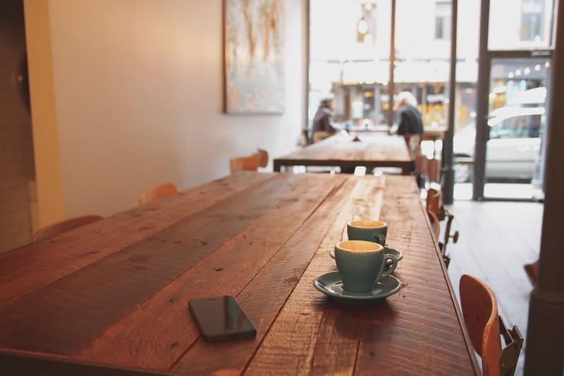 カフェに置かれたコーヒーとiPhone