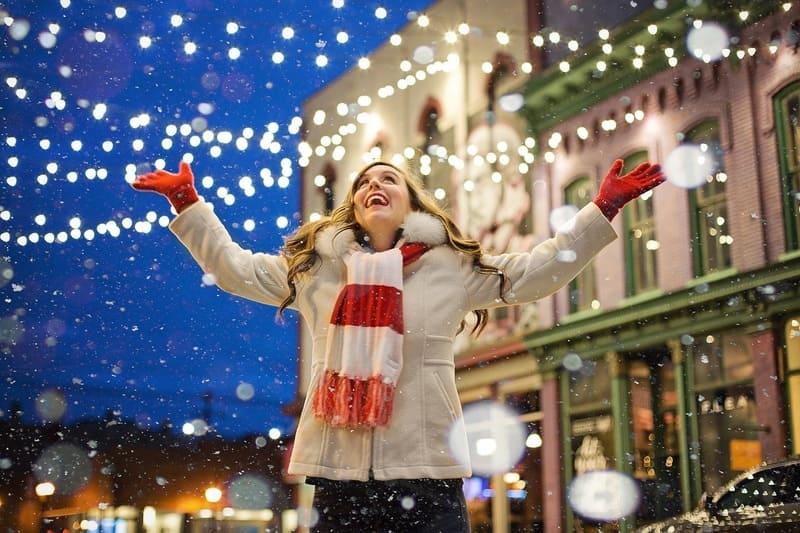 クリスマスの雪と電飾に囲まれた女性