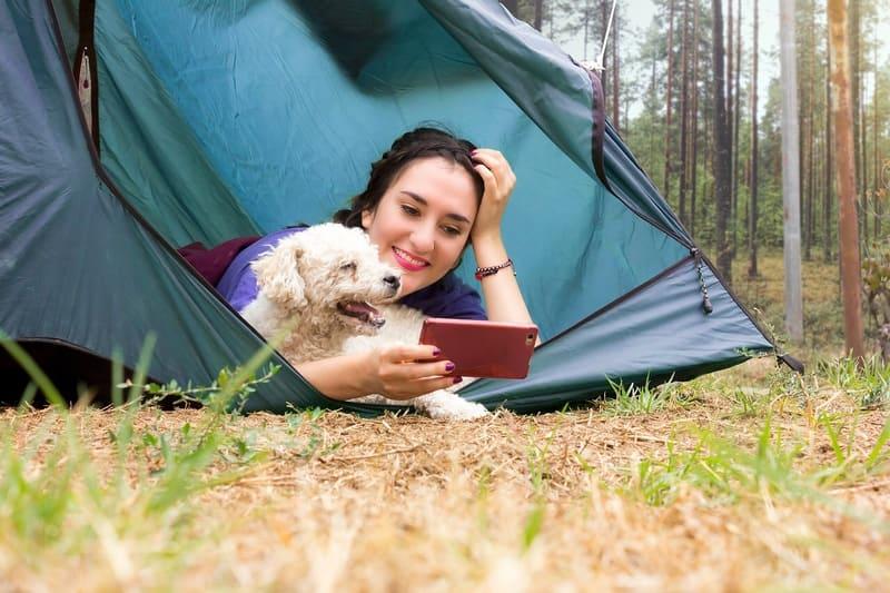 テントに寝ている女性と犬